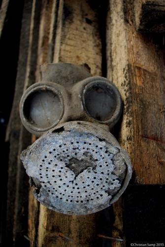 Maska p.gaz na stercie rozebranych desek stropowych