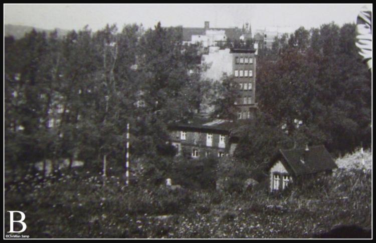 Zdjęcie wykadrowane z fotografii rodzinnej od prawej nieistniejący budynek nastawni kolejowej od lewej uniesiony szlaban przejazdu kolejowego