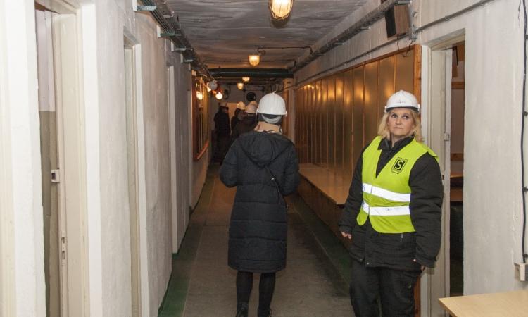 Długi korytarz schronu z szeregiem drzwi po obu stronach